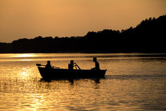 Rowing wooden boat near forest in late evening during sunset people silhouettes Stock Image