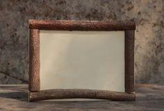 Rown houten kader op de houten achtergrond van de tablewithsteen stock fotografie