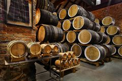 Rows of alcoholic drums in stock. Distillery. Cognac, whiskey, wine, brandy. Alcohol in barrels royalty free stock photo