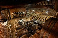 Rows of alcoholic drums in stock. Distillery. Cognac, whiskey, wine, brandy. Alcohol in barrels royalty free stock images