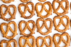 3 rows of baked pretzels on white. A rows of baked pretzels on white with salt stock photography