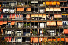 Rows of balconies and windows. Modern building with many rows of balconies and windows with colorful canopies, curtains and different things Royalty Free Stock Photos