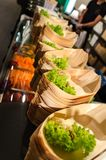 Sushi boats with green garnish. Rows of bamboo boats with green salad garnish and wasabi waitung to be filled with sushi royalty free stock photo