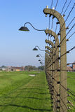 Rows of barbed wire with lanterns across Auschwitz perimeter Royalty Free Stock Image