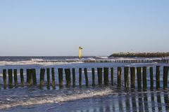 Rows of beacht poldes in the sea with waves and a lighthouse in cadzand in holland in winter and a blue sky. Rows of beach poles and waves in the sea and a stock image