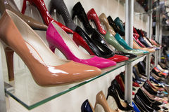Rows of beautiful women's shoes on store shelves Stock Photos