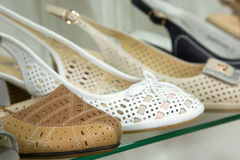 Rows of beautiful women's shoes on store shelves. Royalty Free Stock Images