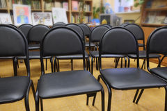 Rows of black chairs. In the hall Stock Photography