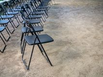 Rows of black metal folding chairs on the ground royalty free stock image