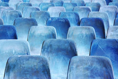 Rows of blue chairs. Rows of broken and stained blue chairs in an outdoor auditorium Stock Image