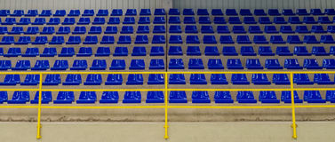 Rows of blue chairs on the podium of the sports hall. Image of rows of blue chairs on the podium of the sports hall Royalty Free Stock Photo