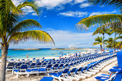 Rows of blue chairs on sunny beach with white sand. Great stirrup cay, Bahamas - January 8, 2016: rows of blue lounge chairs on sunny beach with white sand Stock Photography