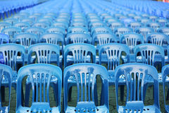 Rows of blue color chairs. In an event field Stock Photos