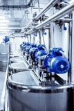 Rows of blue electric motors on tanks for mixing liquids. stock image