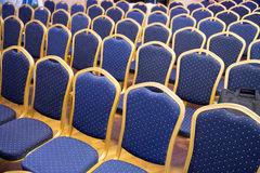 Rows of blue empty seats in unknown event hall. Empty conference chairs in row at a business room.  Comfortable seats in empty corporate meeting office for Stock Photography