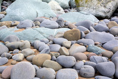 Rows of blue and golden pebble on a beach in the uk Stock Photos
