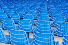 Rows of blue plastic chairs on a metal base. Back view stock photo