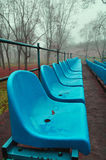 Rows of blue plastic seats in the autumn park in foggy weather. Autumn foggy landscape in vintage tones - rows of blue plastic seats in the autumn park in foggy Stock Photography