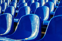 Rows of blue plastic seats in the summer park in nice sunny weather. Selective focus at the central seats Stock Photos