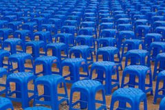 Rows of Blue Plastic Stools. Rows of plastic stools set up as outdoor seating in anticipation of a music concert Royalty Free Stock Image