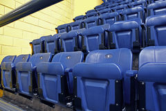 Rows of blue seats. Front rows of new numbered blue plastic arena ice rink seats with yellow concrete block wall Royalty Free Stock Photo
