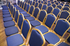 Rows of blue seats in unknown event hall. Group of empty the same chairs with modern backrest and green upholstery in rows at unknown auditorium Stock Photography