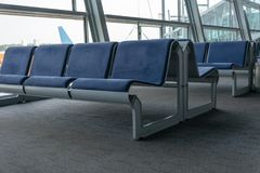 Rows of blue waiting chairs at the airport. With glass windows Stock Image