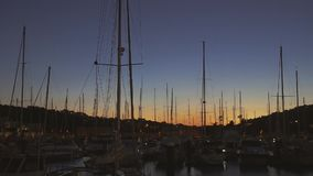 Rows of boats at pier in the evening against sunset skies stock footage