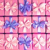 Rows of boxes with gifts decoration ribbon satin bow pink A top view of Flat lay toning. Rows of boxes with gifts decoration ribbon satin bow pink. A top view of stock photos