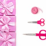 Rows of boxes six with gifts decoration ribbon satin bow scissors pink A top view of Flat lay. Rows of boxes six with gifts decoration ribbon satin bow scissors stock photography