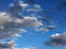 Rows of bright white clouds with gray spots on blue sky background. Royalty Free Stock Image