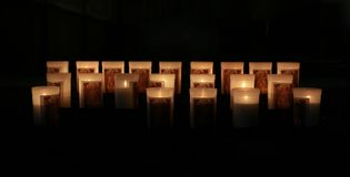 Rows of burning candles in a dim church.  Stock Photos