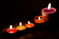 Rows of burning colorful candles. Candle light Royalty Free Stock Photography