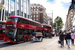 Rows of buses and taxis drive along Oxford Street in London. Oxford Street is one of London`e busiest streets. stock image