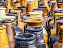 Rows of ceramic freestanding fireplaces. Rows of colorful freestanding ceramic pottery outdoor fireplaces for sale in afternoon sunlight royalty free stock photo