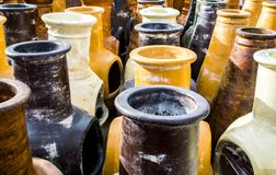 Rows of ceramic freestanding fireplaces. Rows of colorful freestanding ceramic pottery outdoor fireplaces for sale in afternoon sunlight stock photography