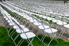 Rows of chairs form a beautiful pattern on the grass land Royalty Free Stock Photography