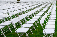 Rows of chairs form a beautiful pattern on the grass land Royalty Free Stock Photos