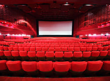 Rows of chairs towards to big screen. Rows of comfortable red chairs towards to big screen in illuminate red room cinema Stock Images