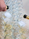 Rows of champagne glasses on table with beautiful bouquet on colorful tablecloth and rustic wooden wall at background. Wedding cer Royalty Free Stock Photo