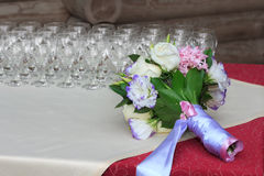Rows of champagne glasses on table with beautiful bouquet on colorful tablecloth and rustic wooden wall at background. Wedding cer Royalty Free Stock Photography
