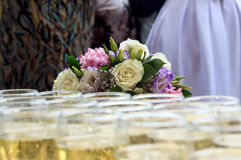 Rows of champagne glasses on table with beautiful bouquet on colorful tablecloth and rustic wooden wall at background. Wedding cer Royalty Free Stock Image