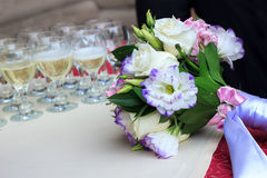 Rows of champagne glasses on table with beautiful bouquet on colorful tablecloth and rustic wooden wall at background. Wedding cer Royalty Free Stock Images