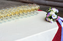 Rows of champagne glasses on table with beautiful bouquet on colorful tablecloth and rustic wooden wall at background. Wedding cer Stock Photos