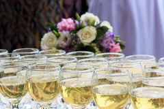 Rows of champagne glasses on table with beautiful bouquet on colorful tablecloth and rustic wooden wall at background. Wedding cer Stock Photography