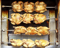 Rows of chickens cooking on a rotisserie Stock Images