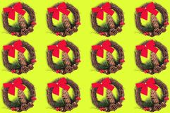 Rows of christmas wreaths with cone and twig of christmas tree and red textile bow and dry branches on yellow background. Seamless pattern royalty free stock photography