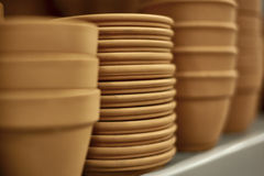 Rows of Clay Pots on a Shelf Royalty Free Stock Photos