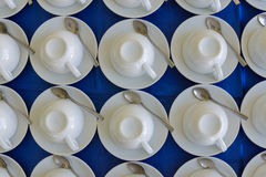 Rows of clean white upside down cups, dish and spoon in a cafeteria or restaurant ready to serve a hot beverage, full frame backgr Stock Photography