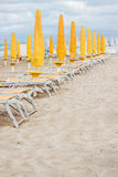 Rows of closed umbrellas and deckchairs on the empty beach Royalty Free Stock Photography